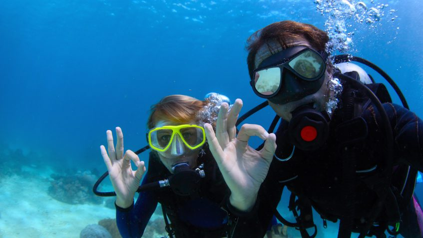 divers with diving masks showing ok sign
