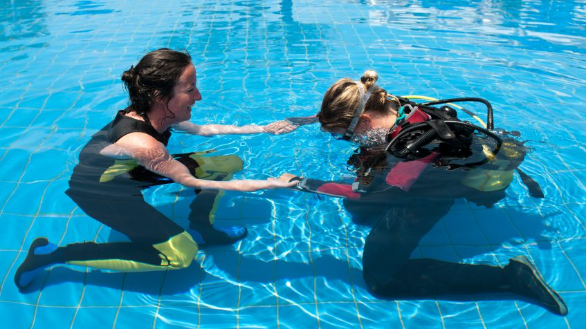 diving instructor with student practicing water nose reflex
